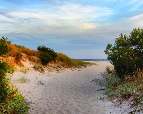 An outdoor swimming pool with patio furniture and chaise lounge chairs alongside multi story resort units.