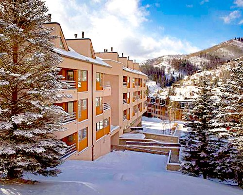 Exterior view of multiple units at Royal Holiday Stream Side At Vail Douglas with wooded area during winter.