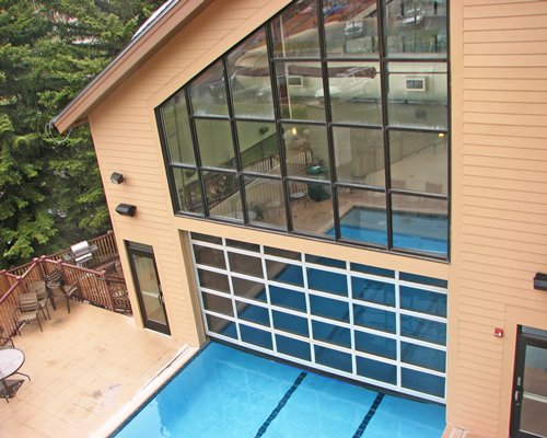 An outdoor swimming pool alongside a unit surrounded by wooded area.