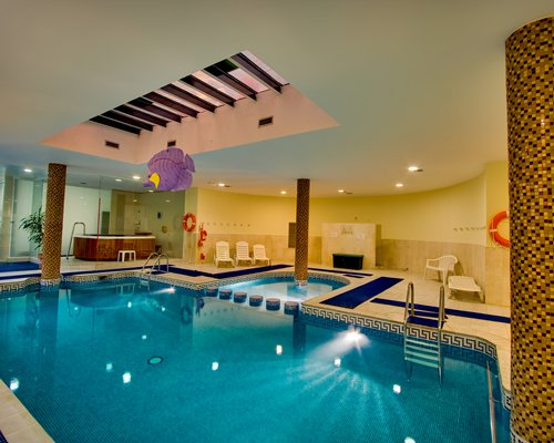 A large indoor swimming pool alongside a hot tub.