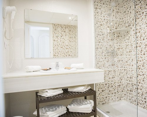 A bathroom with a shower bathtub and a single sink vanity.