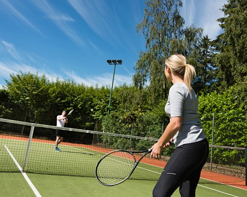A couple playing outdoor tennis .