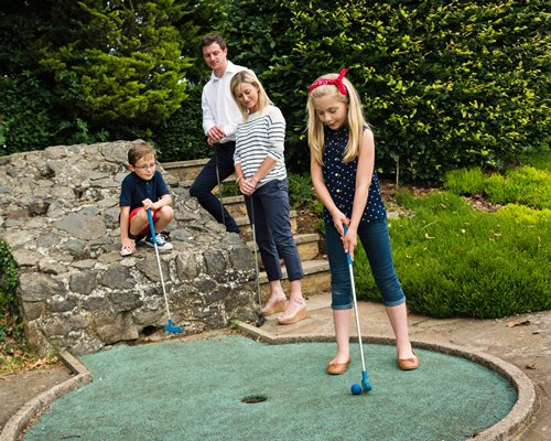 A family playing golf at putt putt golf course.