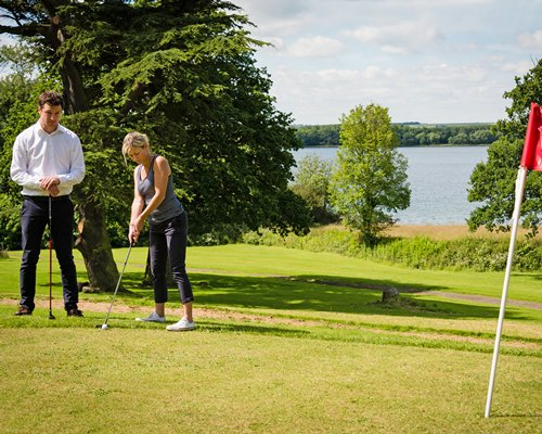 A family playing golf alongside the lake.