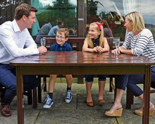 A family sitting at the outdoor dining of Barnsdale Country Club.