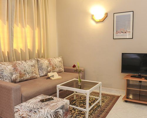 A well furnished living room with a dining area and television.