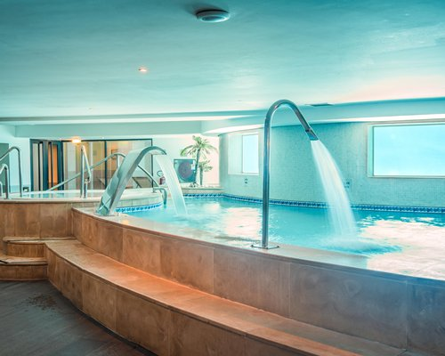 An indoor swimming pool with water curtains and hot tub.