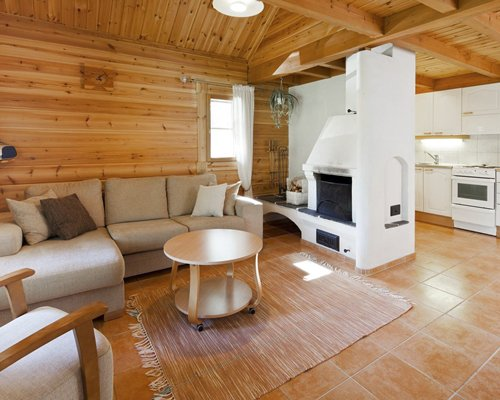 A well furnished living room with fireplace and open plan kitchen.