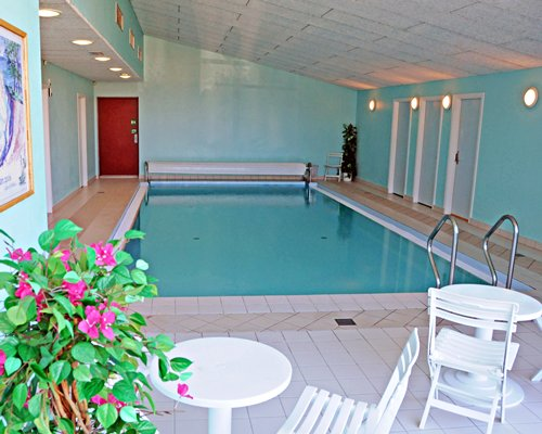 An indoor swimming pool with patio.