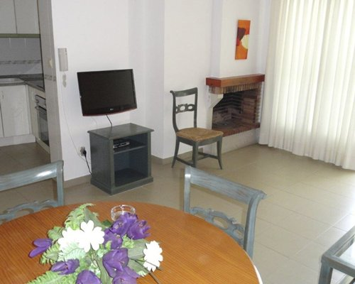 Furnished living room with a television and dining area.