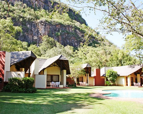 An exterior view of the Sudwala Lodge with patio furniture at the foothills of the mountain.
