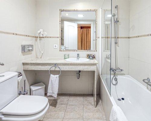 A bathroom with a bath tub and a single sink vanity.