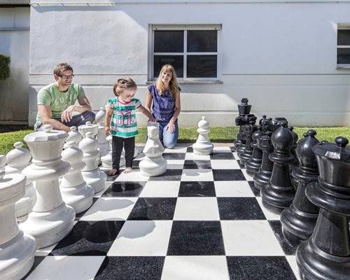 A family playing on a giant chess set.