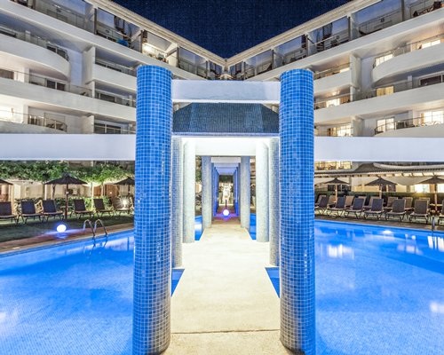 Pathway in between the outdoor swimming pool surrounded by multiple unit balconies.
