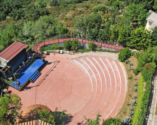 An aerial view of an outdoor venue with a stage alongside wooded area.