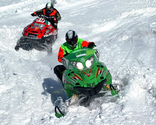 Two people riding snowmobiles.