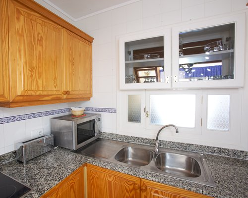 A well equipped kitchen with a microwave and a double sink.
