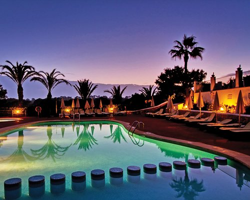 A dusk view of an outdoor swimming pool with chaise lounge chairs.
