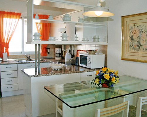 A well equipped kitchen with glass top dining table.
