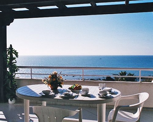 Balcony view of the sea with patio furniture.