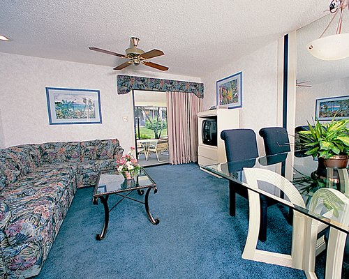 A well furnished living room with television dining area and patio.