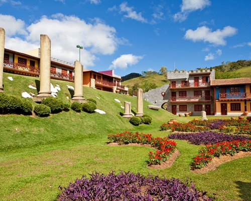 Exterior view of Complexo Hoteleiro Le Canton surrounded by lawn and shrubs.