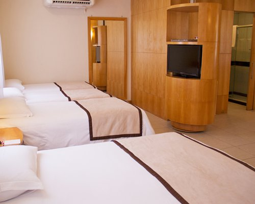 A well furnished bedroom with four beds and a television.