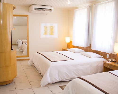 A well furnished air conditioned bedroom with two beds.