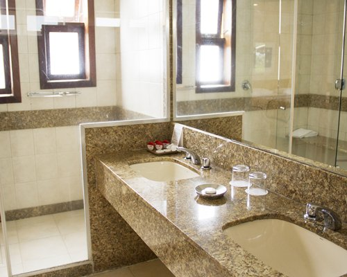 A bathroom with a shower stall and double sink vanity.