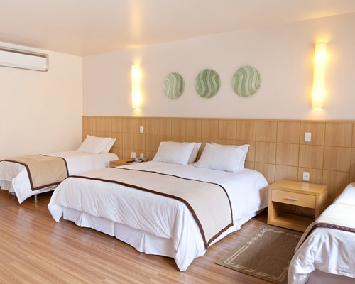A well furnished air conditioned bedroom with three beds.