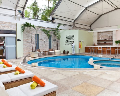 Indoor swimming pool with a kiddie pool and bar.
