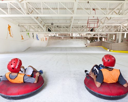 Two people snow tubing in an indoor arena.