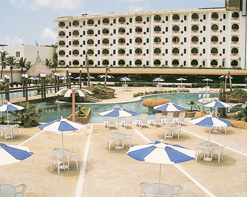 Exterior view of Coral Suites Hotel & Resort with an outdoor swimming pool and sunshades.