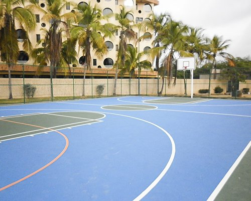 An outdoor basketball court alongside the multi story resort condos.