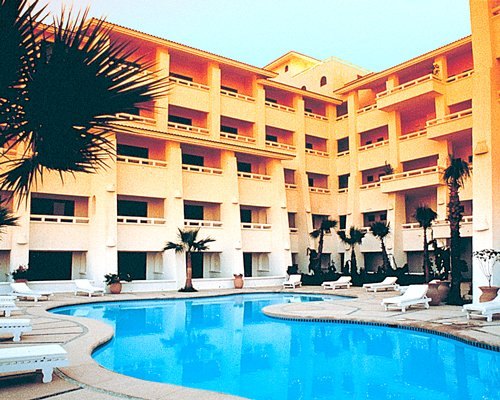 View of multiple unit balconies with outdoor swimming pool chaise lounge chairs and palm trees.