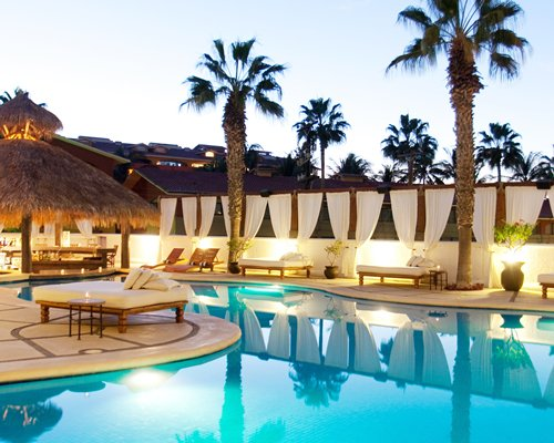 An outdoor swimming pool with thatched sunshades surrounded by palm trees.