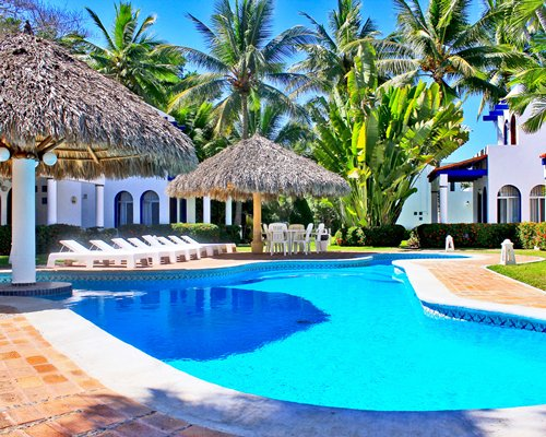 An outdoor swimming pool with chaise lounge chairs and thatched sunshades alongside resort condos.