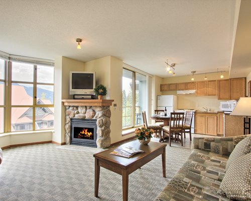 A well furnished living room with open plan kitchen dining area and fire in the fireplace.