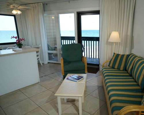 A well furnished living room with sofas and an ocean view.