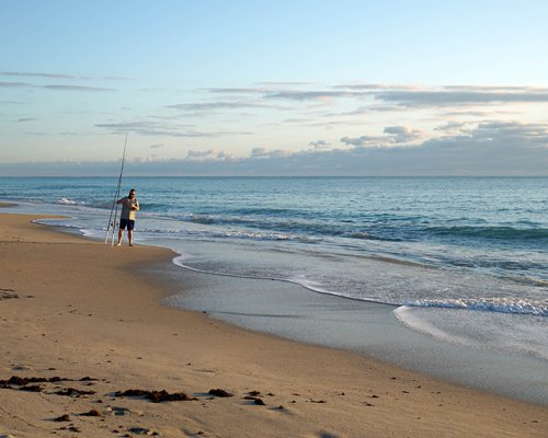 A man on the beach alongside ocean.