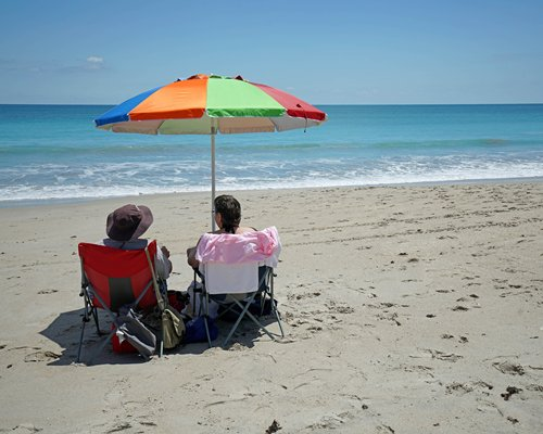 A couple on chaise lounge chairs with sunshade alongside the beach.