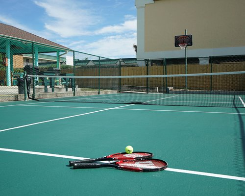 Outdoor recreation area with tennis court and basketball net.