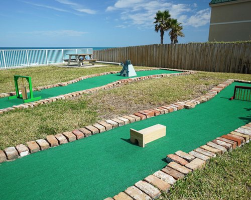 Exterior view with two mini golf sets and a picnic table.
