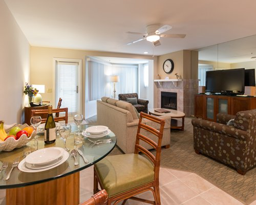 A well furnished living room with television and fireplace alongside the dining area.