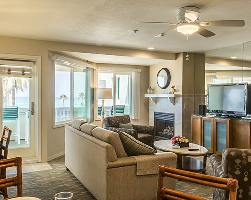 A well furnished living room with television dining area fireplace balcony and ocean view.