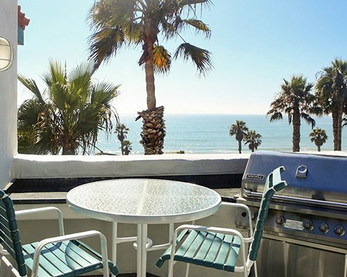 A balcony view with patio furniture and a barbecue grill alongside the ocean.