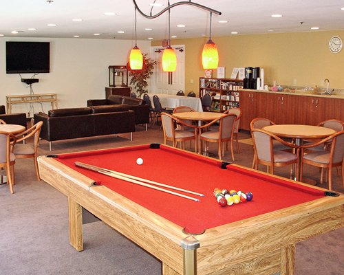 An indoor recreation room with pool table mini library and a television.