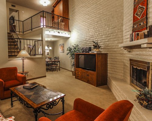 A well furnished living room with a television fireplace and a staircase.