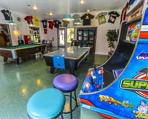 Indoor recreation area with arcade games pool table and air hockey.