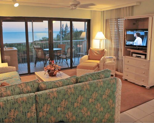 A well furnished living room with television balcony patio furniture.